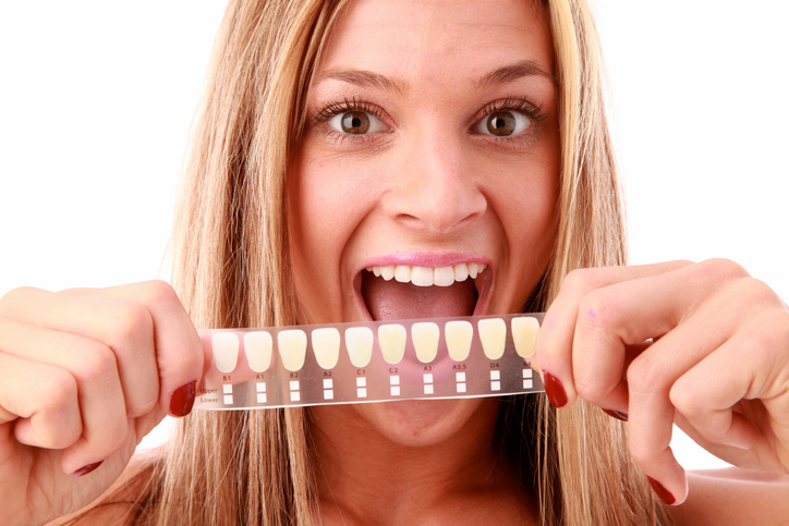Woman holding up teeth whitening results at Ford Dental Group in Huntington Beach, CA